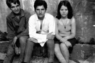 Photo en noir et blanc de trois adolescents dans la cour arrière de la maison familiale.