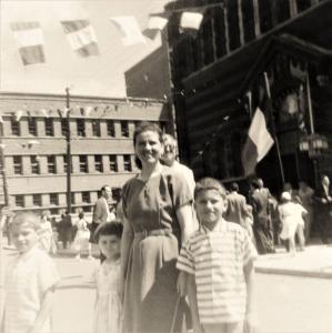 Une femme et ses trois enfants devant l'église italienne Notre-Dame-de-la-Défense. Il y a des gens sur le parvis.
