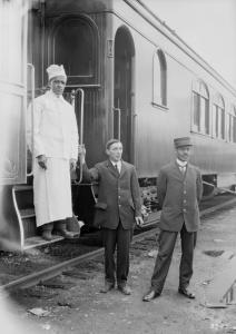 Trois hommes travaillant pour la Compagnie de chemin de fer du Grand Tronc posent devant un wagon