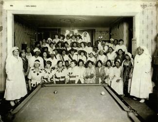Un groupe d'une cinquantaine de femmes noires posent pour le photographe dans une salle où l'on voit une table de billard en avant-plan.