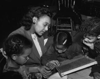 Une jeune femme montre à des enfants comment utiliser un petit métier à tisser.