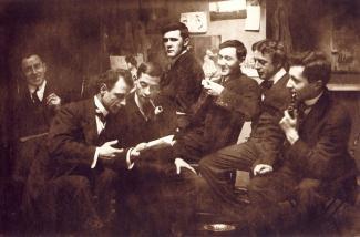Groupe de sept hommes assis fumant la pipe et discutant