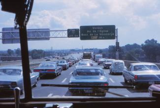 Voitures en file dans les trois voies de l'autoroute 15 sud. On voit le panneau indiquant la sortie vers Verdun et la jonction avec l'autoroute 10.