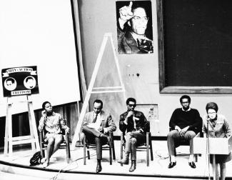 Cinq personnes sont assises sur une estrade lors du Congrès des écrivains noirs