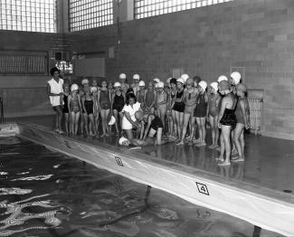 Groupe de jeunes filles autour de la piscine, assistant au cours de sécurité aquatique.