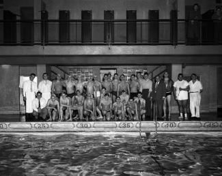 Un groupe d'environ une trentaine d'hommes pose sur le bord de la piscine.