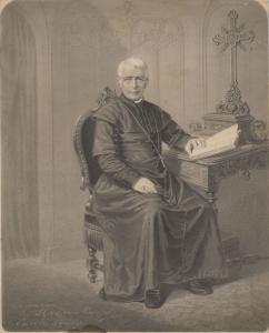 Ignace Bourget, assis à son bureau, un livre est posé sur le bureau.