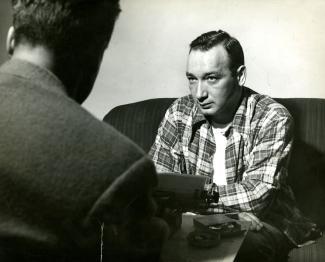 Photographie en noir et blanc, un homme à gauche est dos à l'objectif alors que celui de droite est de face. Il porte une chemise à carreaux.