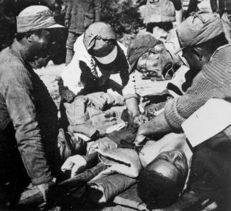 Photo en noir et blanc montrant Bethune opérant un blessé, entouré d'hommes l'assistant.