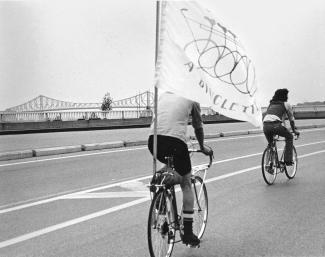 Deux cyclistes circulent avec le pont Jacques-Cartier en arrière-plan, l'un porte un drapeau du Monde à bicyclette.