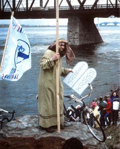 Robert Silverman, déguisé en Moïse, tente de séparer les eaux du fleuve pour gagner l'accès cyclable à la Rive-Sud de Montréal