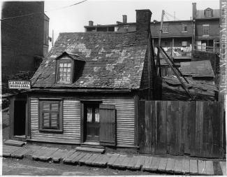 Façade d'une maison ouvrière avec un trottoir en bois devant.