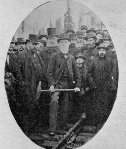 Donald Smith, de la compagnie de chemin de fer Canadien Pacifique, enfonce le dernier crampon de la voie de la première ligne ferroviaire transcontinentale du pays. William Van Horne est à côté de Donald Smith au centre gauche.