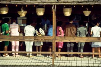 Rangée de personnes debout, de dos, installées devant un comptoir de casse-croûte