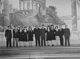 Peinture intérieure dans le hall de l'Empress Theatre, devant laquelle posent les employés en 1944. Le décor en arrière-plan représente le kiosque de Trajan au temple de Philae en Égypte.