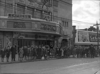 Cette photographie, prise le 30 octobre 1943, montre une file d'enfants devant l'Empress Theatre. Les enseignes lumineuses incitent à soutenir l'effort de guerre canadien par l'achat de bons de guerre.