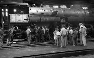 Vue latérale d'une locomotive avec le groupe en visite.