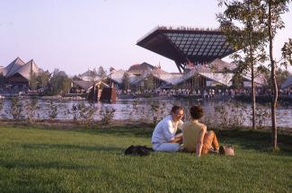 Photo couleur montrant le pavillon du Canada en arrière-plan. En avant-plan, un jeune couple est assis dans l'herbe.
