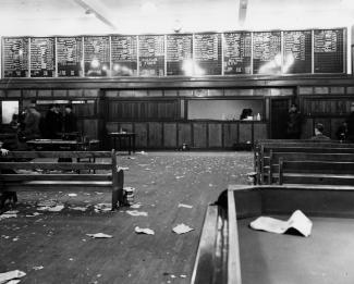 Intérieur d'une salle de paris. Des bancs sont visibles des deux côtés de la pièce et font face à un comptoir de paris. Des papiers jonchent le sol.