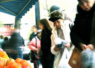 Des gens circulent et regardent les fruits sur un étal sur le trottoir du Quartier chinois