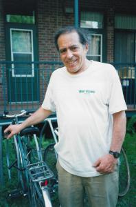 Robert Silverman accoudé à son vélo et portant un t-shirt du Monde à Bicyclette