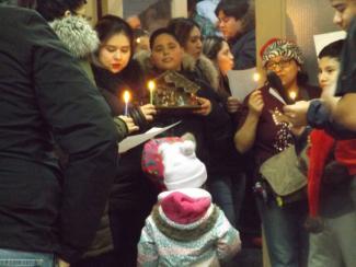 Groupe de personnes de différents âges pour une célébration de Noël. Quelques-uns tiennent des bougies, un tient une crèche.