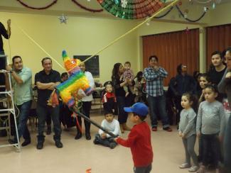 Des adultes et des enfants dans une salle communautaire observent un enfant tapant sur une piñata.