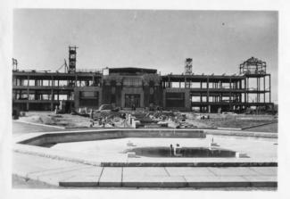 Photographie de l'édifice en cours de construction; on voit les structures du bâtiment.