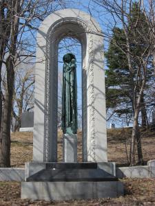 Photographie d'une statue de madone encadrée d'une arche ouvragée.