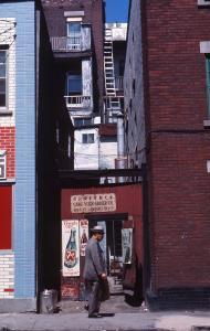 Un homme passe devant une toute petite épicerie prise entre deux édifices plus hauts.