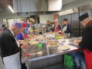Six hommes et femmes préparent des pâtés à la viande dans une cuisine
