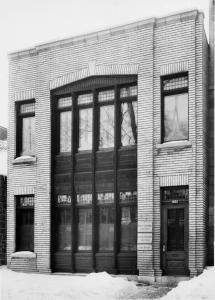 Bâtiment de briques blanches à deux étages avec s fenêtres.