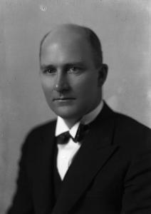 Photographie en noir et blanc d'un homme en plan rapproché taille portant un complet.