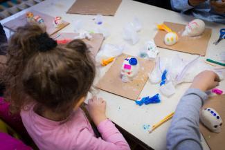 Enfants décorant des crânes pour la Fête des Morts