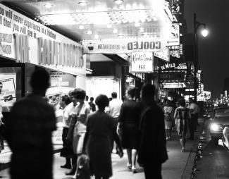 Photographie de la rue Sainte-Catherine éclairée par les enseignes lumineuses, le soir.