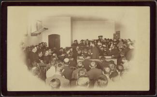 Photographie de Louis Riel, de profil au centre, s'adressant au jury, à gauche.