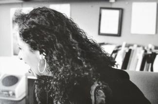Une femme, au longs cheveux noirs, de profil. En arrière-plan, des cadres accrochés au mur et des boites de dossiers.