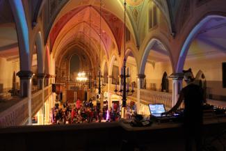 Vue en plongée de la nef d'une église transformée en salle de réception, bondée à l'occasion d'un événement.