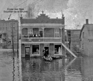 Photo en noir et blanc montrant une rue inondée avec une maison à deux étages en plein centre. Trois hommes sont dans une chaloupe et quelques personnes sont sur le balcon du haut.