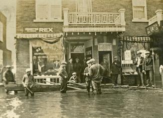 Une douzaine d'hommes sont debout devant un commerce. La rue est inondée. Certains ont les pieds dans l'eau, d'autres sont sur une planche ou dans l'entrée d'un commerce.