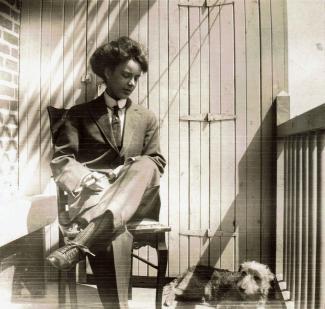 Jeune femme portant un veston et une cravate, assise sur un balcon d'appartement, avec à ses pieds un petit chien.