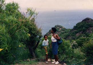 Une mère et sa jeune fille en Guadeloupe, avec la mer en arrière-plan