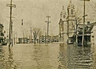 Une place inondée, entourée de maisons et d'une église.