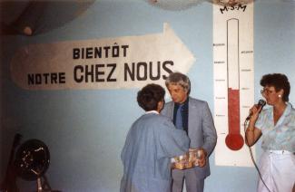 Une bannière à l'effigie d'un thermomètre est affichée au mur. Une femme, de dos, serre la main d'un homme. Une autre est debout et tient un microphone.