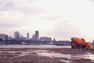 Photo prise de la Cité du Havre en construction montrant un camion orange à l'avant-plan et le Vieux-Montréal à l'arrière-plan