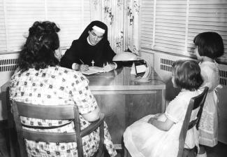 Marie Gérin-Lajoie à un bureau, en entrevue de service social avec une femme et deux jeunes filles.