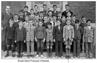 Photo en noir et blanc montrant les garçons d'une classe de 5e année posant devant les portes de l'école à l'extérieur.