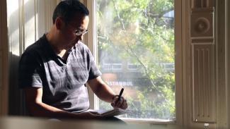 Un homme assis sur le bord d'une fenêtre écrit.