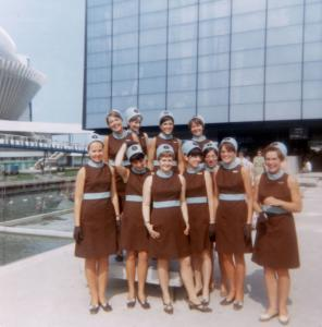 Onze hôtesses en uniforme (sans la veste) debout devant le pavillon du Québec.