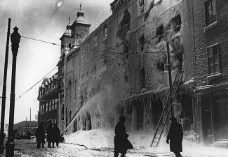 Photographie de pompiers éteignant l'incendie de la cathédrale, dont la façade est endommagée.